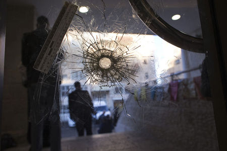 A bullet hole is seen in a door of a synagogue in Jerusalem where two Palestinian militants killed four rabbis and a policeman, November 19, 2014. REUTERS/Ronen Zvulun