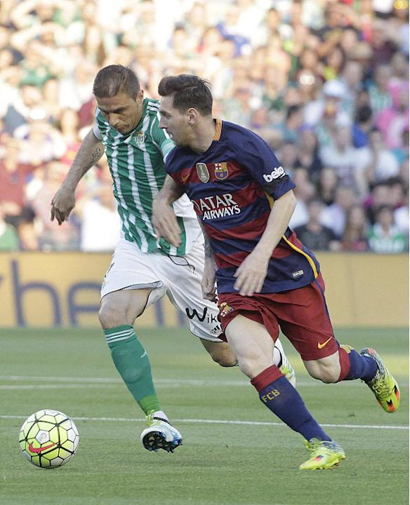Barcelona's, Messi, right, and Betis's, Joaquin Sanchez, left, vie for the ball during their La Liga soccer match at the Benito Villamarin stadium, in Seville, Spain on Saturday, April. 30, 20