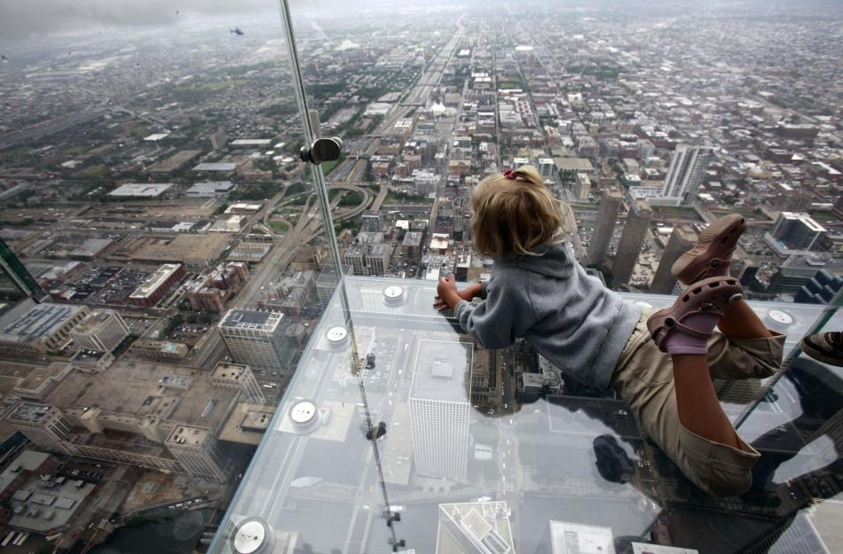 "FILE - In this June 24, 2009, file photo Anna Kane, 5, looks down from ""The Ledge,"" at Chicago's 110 story, 1,450 foot Willis Tower. The glass balcony is suspended 1,353 feet in the air and juts out 4"