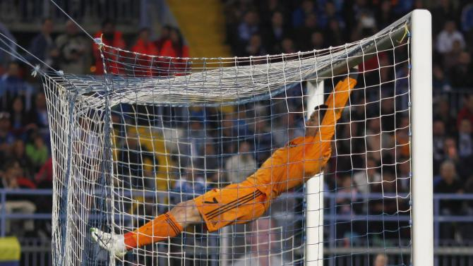 Real Madrid's Cristiano Ronaldo hangs from the crossbar after missing an opportunity to score against Malaga during their Spanish First Division match in Malaga