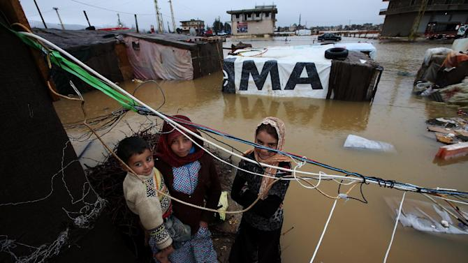 Syrian refugees stand under electricity cables outside their tents, at a temporary refugee camp, in the eastern Lebanese Town of Al-Faour near the border with Syria, Lebanon Tuesday Jan. 8, 2013. Two Syrian refugee encampments in Lebanon's eastern Bekaa valley  were completely immersed in water Tuesday after the Litani river flooded and the water came pouring into their tents. The flood forced dozens of Syrian refugees to leave in search for alternative shelter along with their water-soaked and muddied belongings. (AP Photo/Hussein Malla)