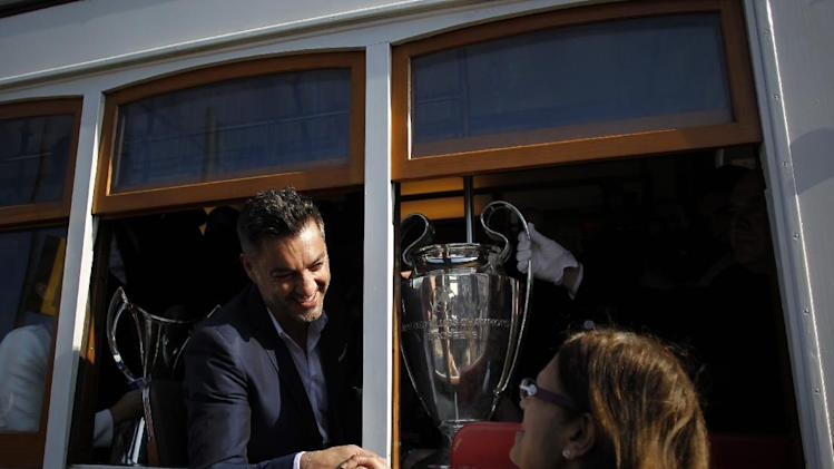 Portugal's former soccer goalkeeper Vitor Baia is greeted by a fan as he holds the Champions League trophy inside a tram before a ride, in Lisbon, Thursday, April 17, 2014. The trophy arrived to the capital prior to the Champions League final match that will take place at Benfica's Luz stadium in Lisbon on May 24