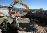 A man talks to Israeli soldiers as a bulldozer demolishes a water well used to irrigate agricultural land in Wadi al-Ghrous, near the West Bank city of Hebron in 2011. Israel demolished dozens of Palestinian homes, water cisterns and farm buildings built with European funds in 2011, aid groups said