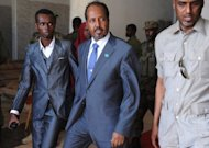 Newly elected Somalia President Hassan Sheikh Mohamud (C) leaves the Jazeera Hotel in Mogadishu after a bomb blast outside the venue