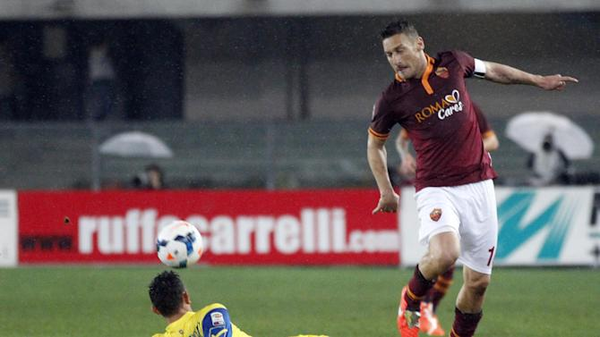 AS Roma's Francesco Totti, right, and Chievo's Ivan Radovanovic, of Serbia, challenge for a ball during a Serie A soccer match at Bentegodi stadium in Verona, Italy, Saturday, March 22, 2014