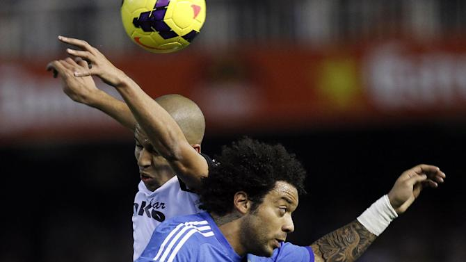 Real Madrid's Marcelo from Brazil duels for the ball with Valencia's Sofiane Feghouli from France  during their La Liga soccer match at the Mestalla stadium in Valencia, Spain, Sunday, Dec. 22, 2013