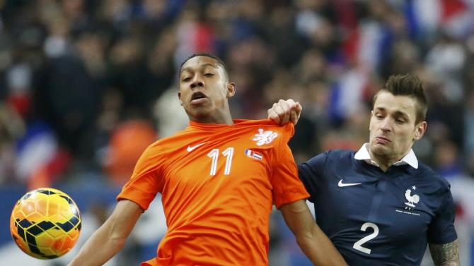 Netherlands' Boetius challenges France's Debuchy during their international friendly soccer match at the Stade de France in Saint-Denis