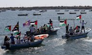 "Palestinians ride on boats at the port of Gaza City during a rally in support of the Gaza-bound international Freedom Flotilla on July 2. Greece tried to appease furious activists after halting a flotilla bound for Gaza, offering to deliver aid ""through existing channels"" and reaching out to the Palestinian Authority Sunday"