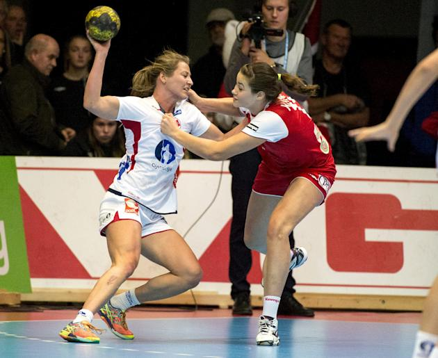Norway's Sanna Solberg (L) is challenged by Belarus' Maryia Kanaval during their qualifying match for the 2016 Women's European Handball Championship in Trondheim
