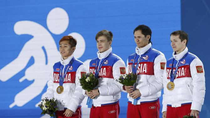 Gold medallists Russia's An, Elistratov, Grigorev and Zakharov celebrate during the victory ceremony for the men's 5,000 metres relay short track speed skating event at the 2014 Sochi Winter Olympics in Sochi