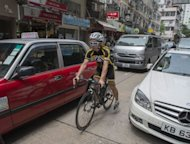A cyclist makes his way through traffic in Hong Kong. On Hong Kong's traffic-heavy streets, horns blare as red taxis, double-decker buses and minivans shuttle people to work. But there is one thing missing -- bicycles