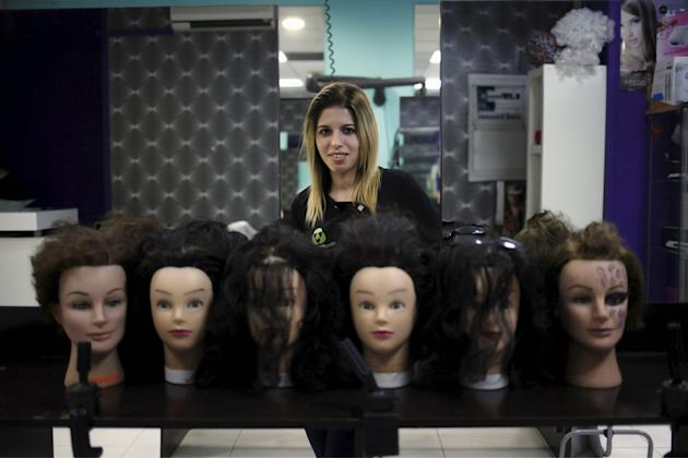 Desire Vargas, 20, poses for a photo at a hairdressing salon where she studies a course in beauty and hairdressing, in downtown Ronda, near Malaga, southern Spain