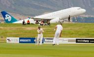New Zealand's BJ Watling (front L) bats as an Air New Zealand plane takes off on the last day of the four day warm-up match between New Zealand XI and England, in Queenstown, on March 2, 2013