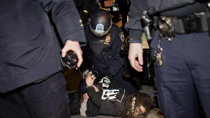 """Police officers arrest a demonstrator during after a vigil held for Kimani """"Kiki"""" Gray in the East Flatbush neighborhood of New York's Brooklyn borough, Wednesday, March 13, 2013, in New York. According to the NYPD, the teen pointed a .38-caliber revolver at the plainclothes officers, who responded by shooting him to death. (AP Photo/John Minchillo)"""