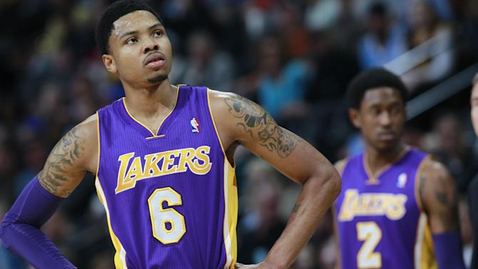 Los Angeles Lakers guard Kent Bazemore, front, looks on against the Denver Nuggets as guard MarShon Brooks, back, checks in to play in the first quarter of an NBA basketball game in Denver on Friday, March 7, 2014