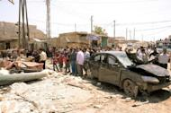Handout photo from the Syrian Arab News Agency shows residents gathered around the reckage caused by a car bomb in the Syrian city of Aleppo on May 5. Syria's authorities and the opposition traded accusations Sunday over who was behind blasts that rocked Damascus and Aleppo, on the eve of parliamentary polls designed to boost the regime's legitimacy