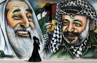 A Palestinian woman walks past a mural depicting late Hamas spiritual leader Sheikh Ahmed Yassin (left) and late Palestinian leader Yasser Arafat (right) in Gaza City in July. A Swiss radiology lab said Friday it will test the remains of Arafat for polonium poisoining after receiving the go-ahead from his widow
