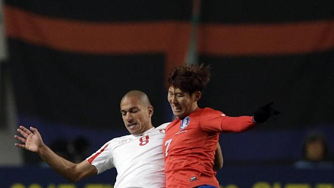 Switzerland's Gokhan Inler, left, fights for the ball against South Korea's Son Heung-min during their friendly soccer match at Seoul World Cup Stadium in Seoul, South Korea, Friday, Nov. 15, 2013. South Korea won 2-1