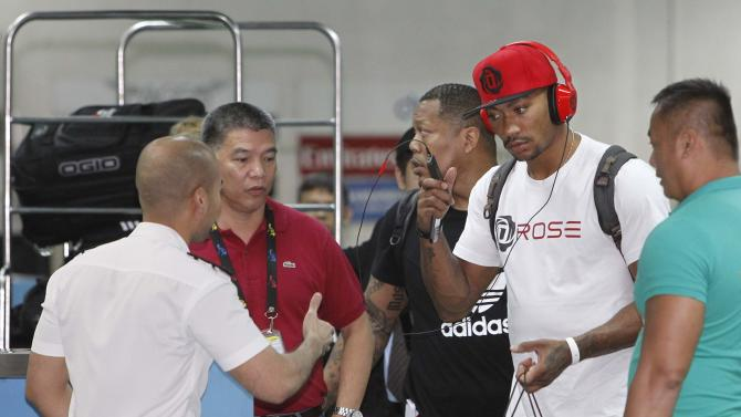 A customs officer extends a handshake to welcome NBA star Derrick Rose upon his arrival for his Asia tour at the Manila International Airport