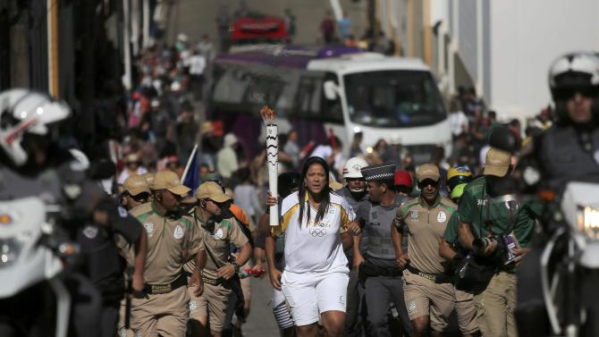 Former volleyball player Santos carries the Olympic torch in the streets of Sao Luiz do Paraitinga