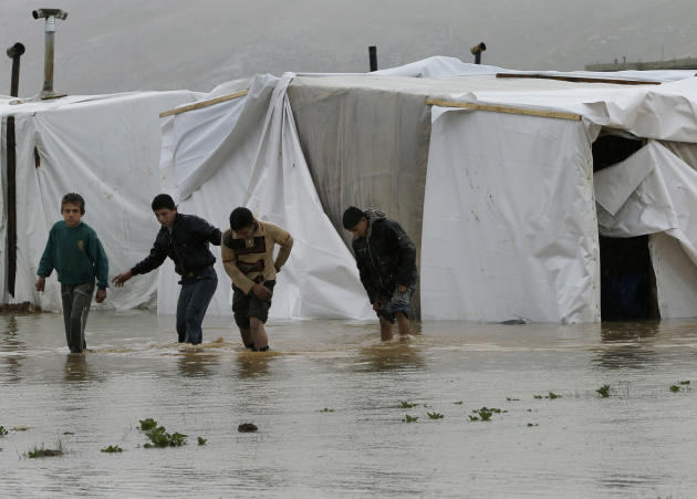 Syrian refugee boys make their way in flooded water at a temporary refugee camp, in the eastern Lebanese Town of Al-Faour near the border with Syria, Lebanon, Tuesday, Jan. 8, 2013. Two Syrian refugee