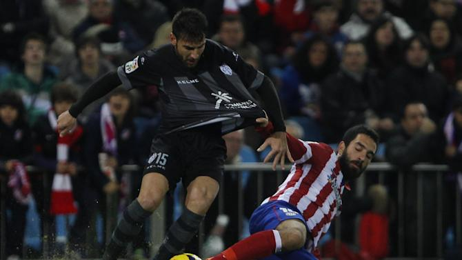 Atletico's Arda Turan from Turkey, right, competes with Nikos Karampelas from Greece, left, during a Spanish La Liga soccer match between Atletico de Madrid and Levante at the Vicente Calderon stadium in Madrid, Spain, Saturday, Dec. 21, 2013