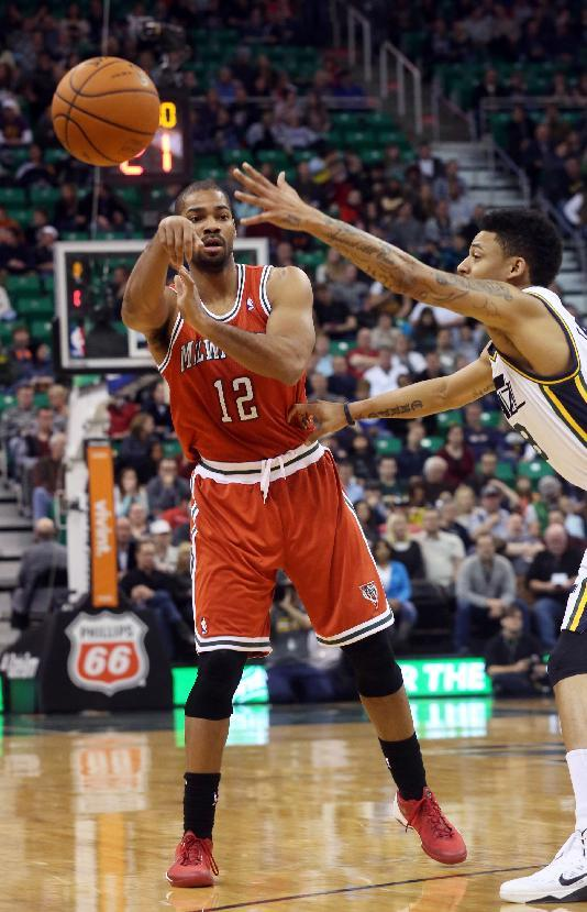 Milwaukee Bucks' Gary Neal (12) passes the ball past Utah Jazz's Diante Garrett, right, in the first half of an NBA basketball game Thursday, Jan. 2, 2014, in Salt Lake City
