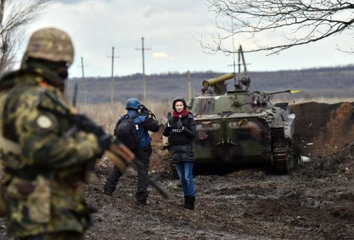 A TV journalist prepares to do a piece to camera on the frontline between Ukrainian forces and pro Russian separatists near Debaltseve in the Donetsk region on December 24, 2014