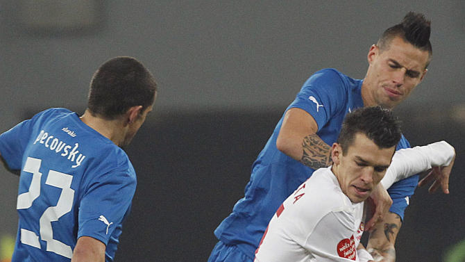 Poland's Waldemar Sobota, center, competes for the ball with Slovakia's Viktor Pecovsky, left, and Marek Hamsik,right, during their friendly soccer match in Wroclaw Poland, Friday, Nov. 15, 2013
