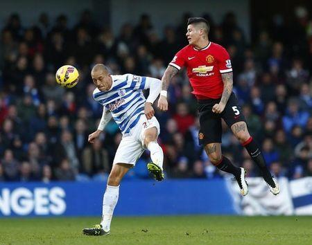 Queens Park Rangers' Bobby Zamora is challenged by Manchester United's Marcos Rojo during their English Premier League soccer match, at Loftus Road in London