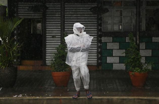 Filipino Efren Villamor, 62, wears plastic sheets to shield him from rain as Tropical Storm Linfa enhanced the southwest monsoon in Manila, Philippines on Sunday, July 5, 2015. Tropical Storm Linfa bl