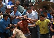 Egyptian protesters beat a man who they accused of attacking them in the Abbassiya district in Cairo. Twenty people were killed in clashes as attackers stormed an anti-military protest near the defence ministry in Cairo, medics said