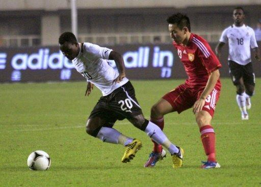 Ghana's Kwadwo Asamoah (L) tussles for the ball against China's Liu Jianye