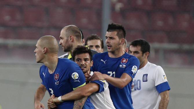 Greece's Sotiris Ninis (18) holds Slovakia's captain Martin Skrtel (3) as he tries to attack against a Greek player after their World Cup Group G qualifying soccer match at the Karaiskaki stadium in the port of Piraeus, near Athens, Friday, Oct. 11, 2013. Greece won 1-0