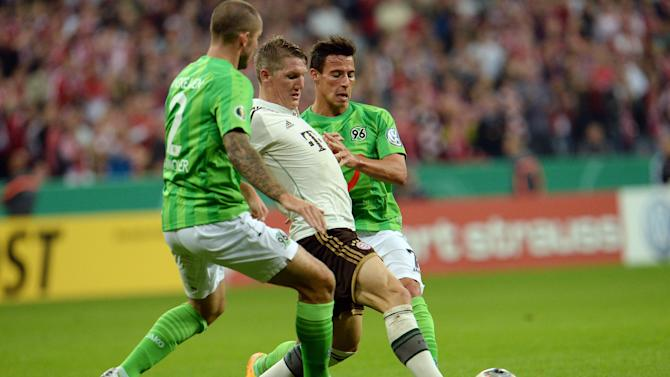 Munich's Bastian Schweinsteiger, center, challenge for the ball with Hannover's Leon Andreasen of Denmark, left, and Edgar Prib during the German soccer cup second round match between FC Bayern Munich and Hannover 96 , in Munich, southern Germany, Wednesday, Sept. 25, 2013