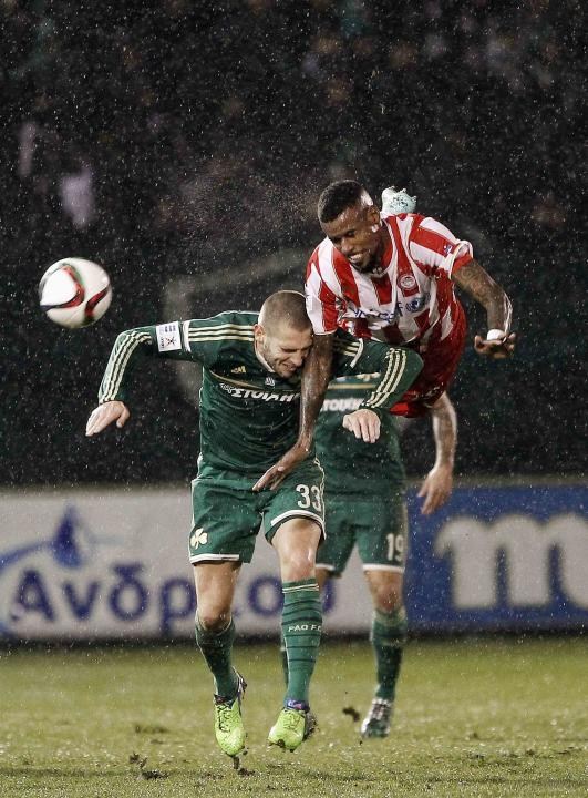 Olympiakos' Santana jumps for the header next to Panathinaikos' Petric during their Greek Super League soccer match under heavy rainfall in Athens