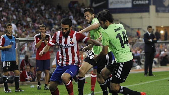Atletico de Madrid's Arda Turan from Turkey, left, in action with Osasuna's Alejandro Arribas, right, and Damia Abella, centre, during a Spanish La Liga soccer match at the Vicente Calderon stadium in Madrid, Spain, Tuesday, Sept. 24, 2013