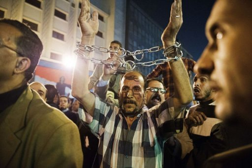 An Egyptian man with his wrists bound by a chain joins thousands of Egyptian protesters as they rally and shout slogans against Egyptian security forces during clashes with police. Protesters clashed with police in the Egyptian capital on on Monday leaving dozens injured on the first anniversary of street battles that left 45 demonstrators dead, witnesses said