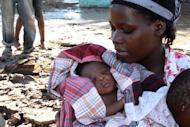 Rofino, a baby born on the roof of his mother's house while floodwaters were raging past, is held by his mother in Guija, southern Mozambique on January 27, 2013. Intense flooding in Mozambique has displaced at least 150,000 people, the United Nations said Monday, with the figure expected to rise further as fresh rains spread flooding northward