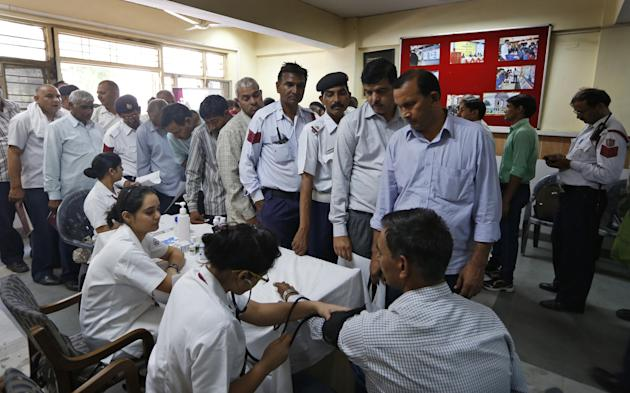 Delhi Traffic Police constables stand in a queue for a medical check up, particularly for respiratory problems, in New Delhi, India, Wednesday, May 6, 2015. Air pollution kills millions of people ever