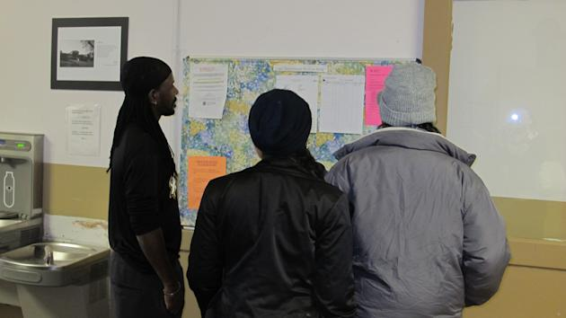 In a Jan. 15, 2015 photo, asylum-seekers staying at the Vive La Casa shelter in Buffalo, N.Y., check to see whether they have been scheduled for an interview with Canadian immigration officials the fo