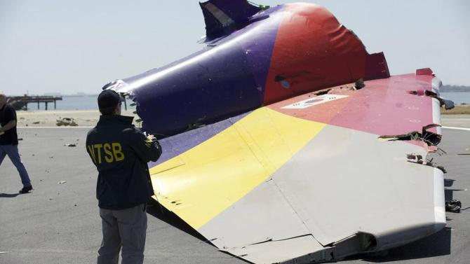 NTSB handout file photo shows an investigator looking at the the wreckage of Asiana Airlines Flight 214 that crashed at San Francisco International Airport