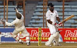 England's Michael Carberry (R) plays a ball as Bangladesh's wicketkeeper Mushfiqur Rahim (L) tries to catch during their third day of first test cricket match of the series in Chittagong March 14, 2010. REUTERS/Andrew Biraj/Files