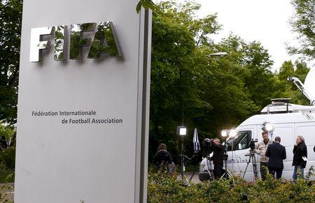 Members of the media stand in front of the entrance of the FIFA headquarters in Zurich