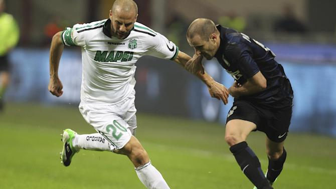 Inter Milan forward Rodrigo Palacio, right, of Argentina, challenges for the ball with Sassuolo defender Paolo Bianco during the Serie A soccer match between Inter Milan and Sassuolo at the San Siro stadium in Milan, Italy, Sunday, Feb. 9, 2014