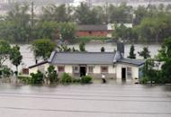 A man cleans his house at Wuche in eastern Ilan county, as typhoon Saola approches the Taiwan's east coast on August 2, 2012. As many residents across the island woke up to see their neighborhoods covered in ankle-deep water, classes and work were suspended everywhere, except for Taidong county in the southeast