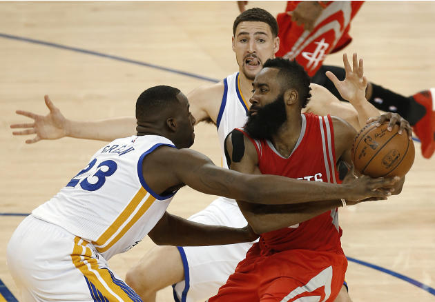 Houston Rockets guard James Harden, right, is defended by Golden State Warriors forward Draymond Green (23) and guard Klay Thompson during the second half of Game 2 of the NBA basketball Western Confe