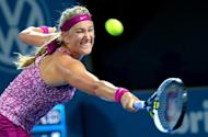 Victoria Azarenka of Belarus hits a backhand return to Casey Dellacqua of Australia in their match at the Brisbane International tennis tournament, in Brisbane on January 1, 2014