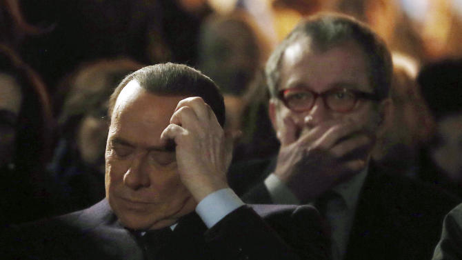 """Former Italian Premier Silvio Berlusconi, foreground, sits in front of Norther League party's leader Roberto Maroni in Milan, Italy, Sunday, Jan. 27, 2013. Silvio Berlusconi says Benito Mussolini did much good, except for dictator's regime's anti-Jewish laws. Berlusconi also defended Mussolini for siding with Hitler, saying the late fascist leader likely reasoned that German power would expand so it would be better for Italy to ally itself with Germany. He was speaking to reporters Sunday on the sidelines of a ceremony in Milan to commemorate the Holocaust. When Germany's Nazi regime occupied Italy during World War II, thousands from the tiny Italian Jewish community were deported to death camps. In 1938, before the war's outbreak, Mussolini's regime passed anti-Jewish laws, barring them from universities and many professions, among other bans. Berlusconi called the laws Mussolini's """"worst fault"""" but insisted that in many other things, """"he did good."""" (AP Photo/Antonio Calanni)"""