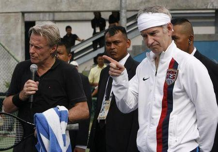 Bjorn Borg and John McEnroe speak with participants during tennis clinic at National Tennis Development Center in Bangkok